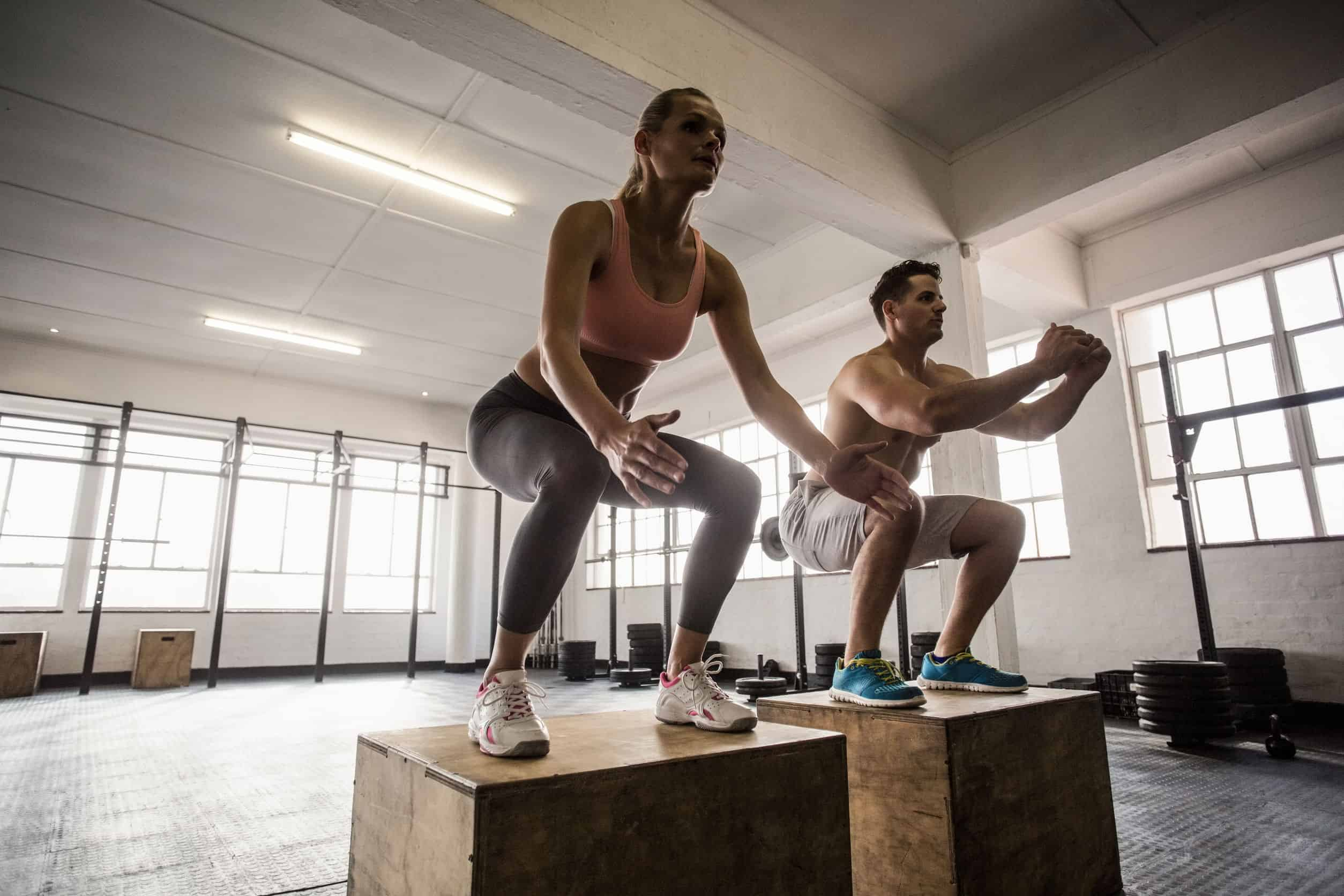 45650271 - muscular couple doing jumping squats in crossfit gym